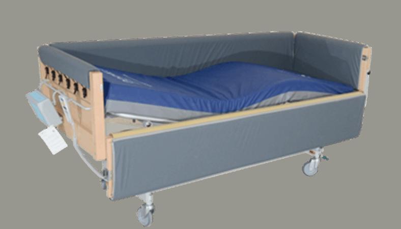 En plejeseng med gråt betræk på siderne. Sengens ene side står åben, så madrassen er synlig. Den er blå på oversiden og grå på undersiden
