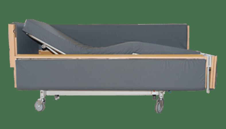Et billede af en plejeseng med polstrede sider i gråt betræk. Madrassen er hævet op i hovedenden. I fodenden er gavlen åben, og siden er åben.