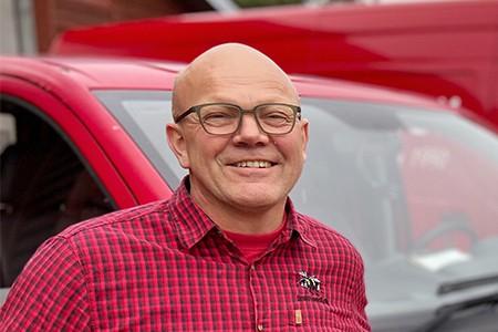 Et portræt af Rasmus Henriksen, indehaver af Jysk Handi. Han har briller og smiler. Han har en rød ternet skjorte på med Jysk Handis logo.