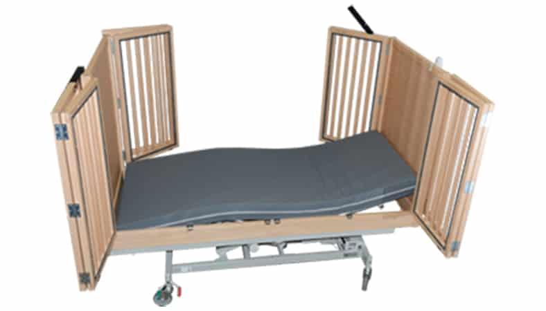 En plejeseng med høje sider. Tremmerne i den ene side står på klem, mens de i siden nær kameraet står helt åbne og giver fri adgang til madrassen