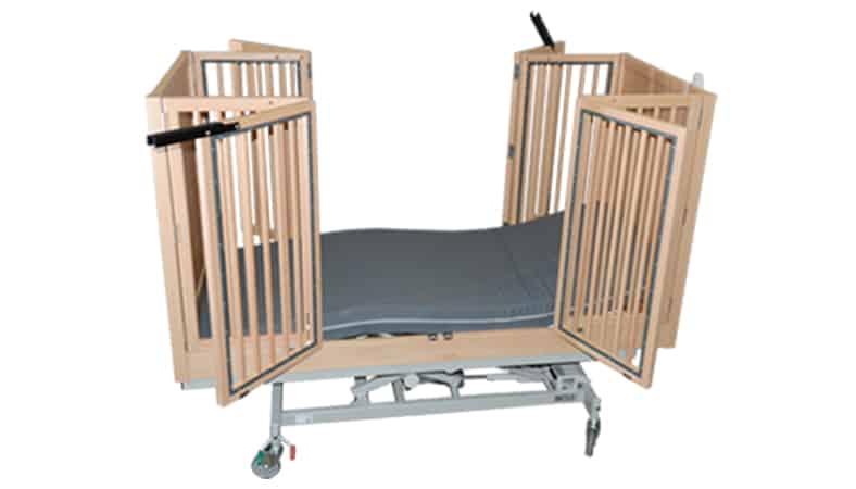 En plejeseng med høje sider i tremmer. Begge sider står åbne, så man kan se madrassen.