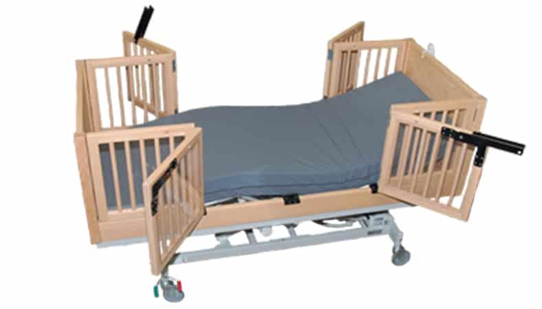 en plejeseng med tremmer i siderne og lukkede gavle har åbnede sider, så to hjælpere kan komme til på samme tid