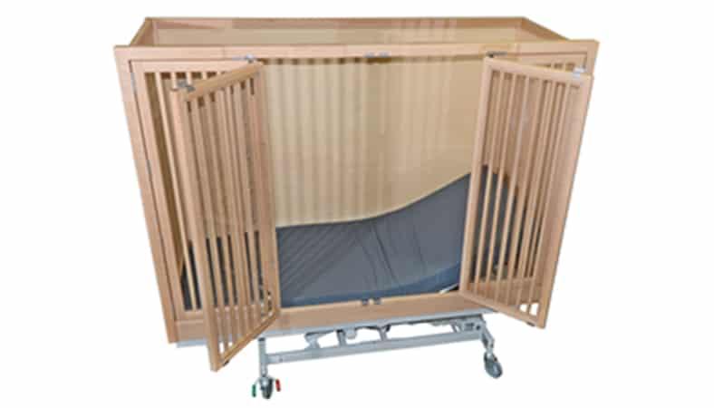 En plejeseng med høje sider. Siden mod kameraet har tremmer og låger, som står åbne, så man kan se madrassen