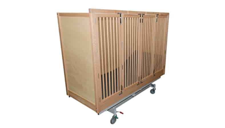 En seng med høje sider. Gavlene og den ene side er lukket med træplader. Siden ud mod kameraet består af tremmer, som man kan se sengens madras imellem